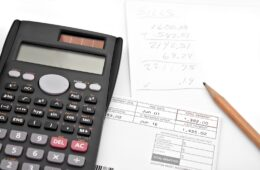 A calculator and papers for adding up the monthly bills isolated over white. Use a digital style font to create your own message on the LCD screen.