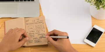 Designer drawing a sketch of new website, view from above